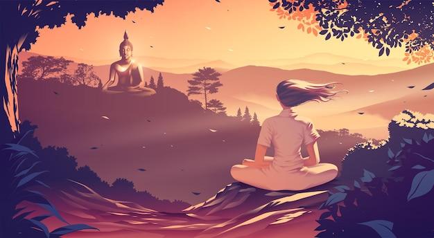 Una giovane donna sta meditando sulla cima di una montagna