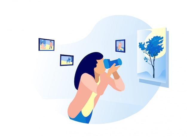 Giovane donna che fa le immagini nell'esposizione del museo