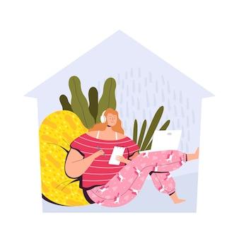 Una giovane donna in pigiama è seduta a casa e studia online.