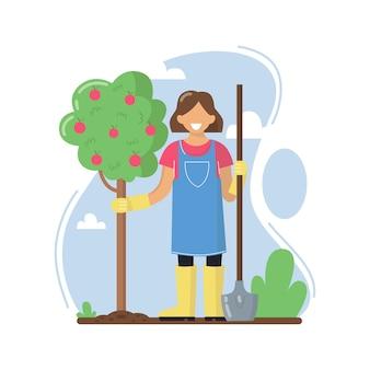 Una giovane donna ha piantato un albero di mele. una donna lavora in giardino.