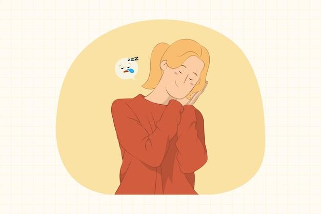 Giovane donna che dorme con le mani giunte sotto il concetto di guancia