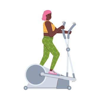 Giovane donna che si allena sulla macchina ellittica in palestra o a casa a