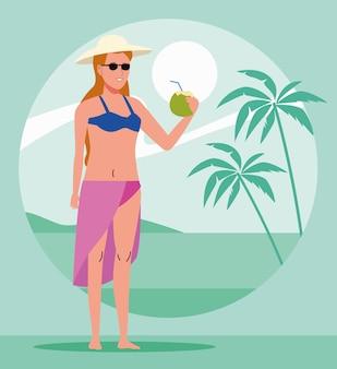Giovane donna che indossa il costume da bagno bere cocktail di cocco