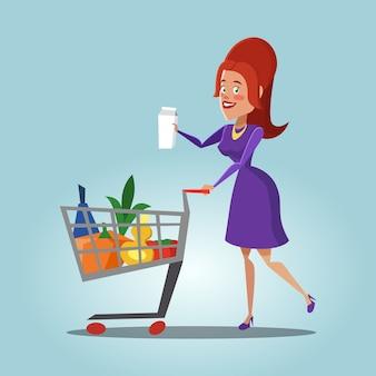Giovane donna con un carrello pieno di prodotti freschi. cibo salutare.