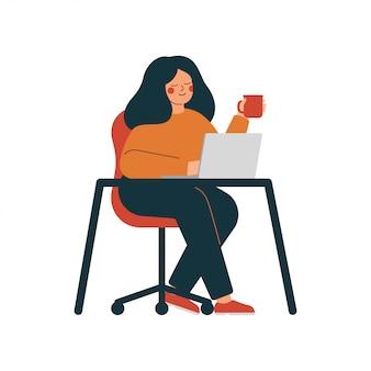 La giovane donna lavora al computer portatile che beve il tè. ufficio a casa