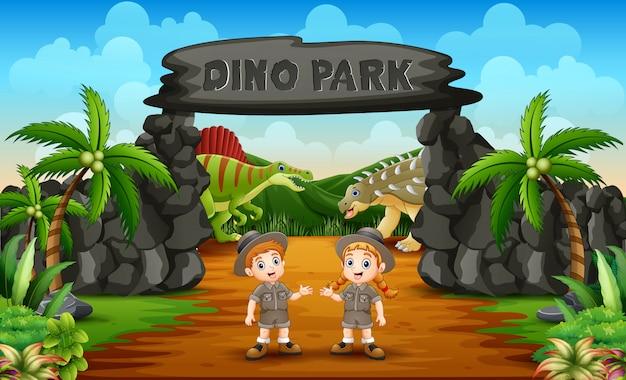 Ragazzo e ragazza del guardiano dello zoo sull'entrata del parco di dino