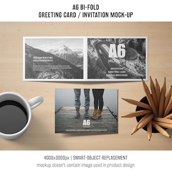 A6 mockup di biglietti d'invito bi-fold con caffè