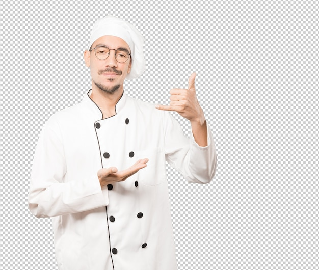 Aarzelende jonge chef-kok die een gebaar maakt van bellen met de hand