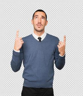 Aarzelende jonge man die met zijn vinger omhoog wijst