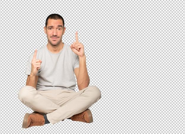 Aarzelende jongeman die met zijn vinger omhoog wijst