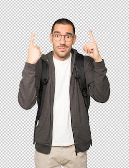 Aarzelende student die met zijn vinger omhoog wijst
