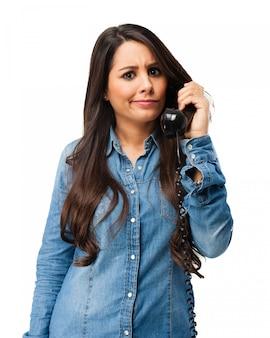 Adolescente preocupada hablando por teléfono