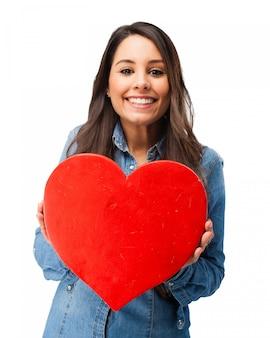 Adolescente romántica sujetando un corazón