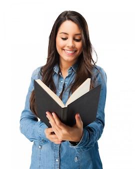 Adolescente sonriente leyendo un libro