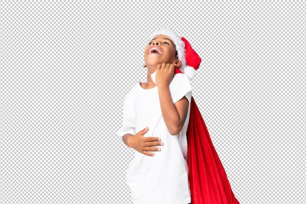 Afrikaanse amerikaanse jongen met kerstmishoed en het nemen van een zak met giften