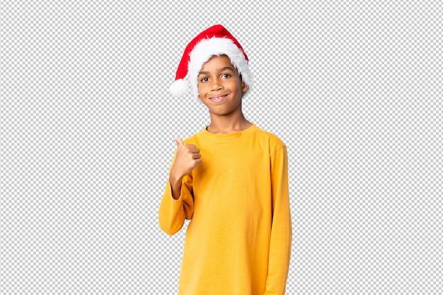 Afro-amerikaanse jongen met kerstmuts met duimen omhoog omdat er iets goeds is gebeurd