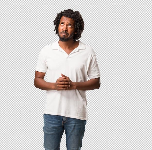 Afroamericano guapo dudando y confundido, pensando en una idea o preocupado.