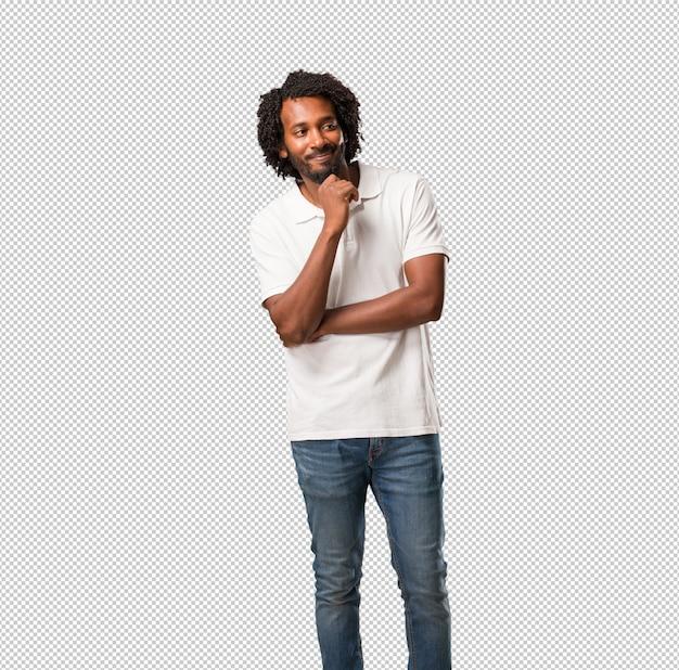 Afroamericano guapo pensando y mirando hacia arriba, confundido sobre una idea