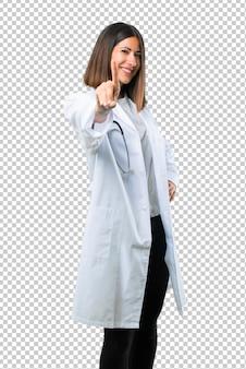 Aggiusti la donna con lo stetoscopio che mostra e che alza un dito nel segno del meglio