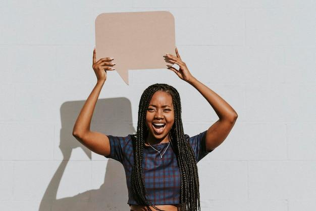 Alegre mujer negra mostrando un bocadillo en blanco
