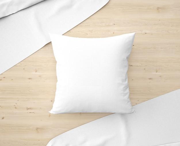 Almohada blanca con sábanas en el suelo