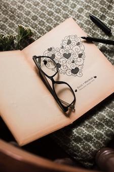 Alto angolo di libro con occhiali e penna