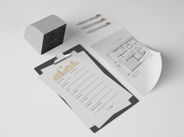 Alto ángulo de bloc de notas con papeles y plano