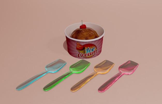 Alto ángulo de envase de helado con cucharas de plástico de colores.