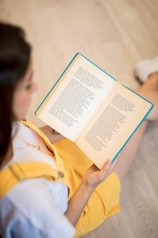 Alto ángulo de una niña leyendo en la biblioteca