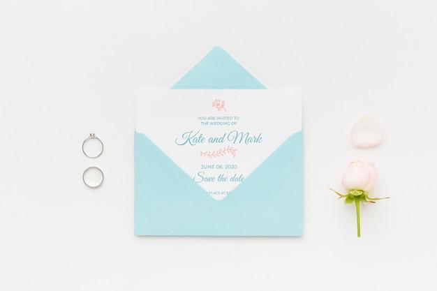Anillos de boda y maqueta de invitación con flor