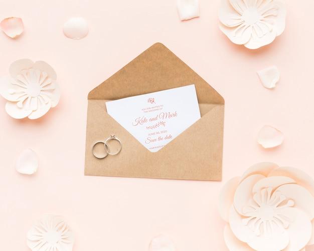 Anillos de boda y maqueta de invitación con flores de papel y pétalos.