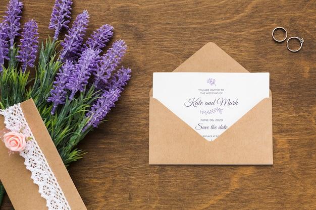 Anillos de boda y maqueta de invitación con lavanda
