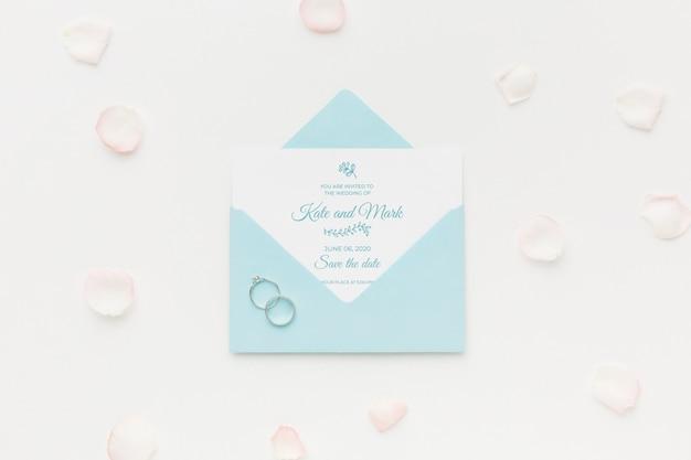 Anillos de boda y maqueta de invitación con pétalos