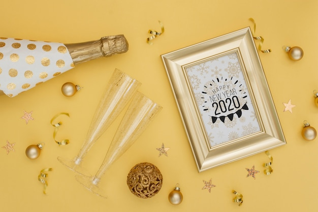 Año nuevo 2020 con botella dorada de champagne y copas