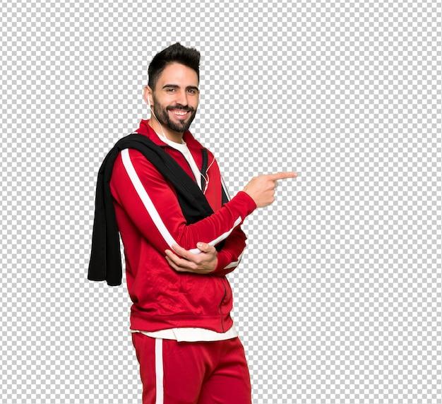 Apuesto deportista apuntando el dedo hacia un lado en posición lateral