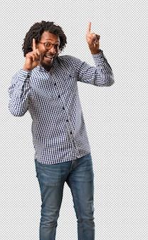 Apuesto empresario afroamericano apuntando hacia un lado, sonriendo sorprendido presentando algo, natural y casual