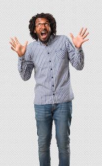 Apuesto empresario afroamericano gritando feliz, sorprendido