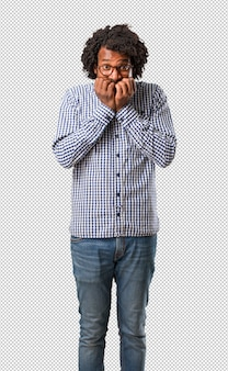 Apuesto empresario afroamericano mordiéndose las uñas, nervioso y muy ansioso y asustado por el futuro, siente pánico y estrés