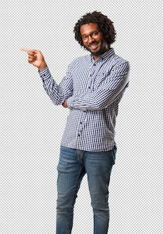 Apuesto hombre afroamericano de negocios apuntando hacia un lado, sonriendo sorprendido presentando algo, natural y casual