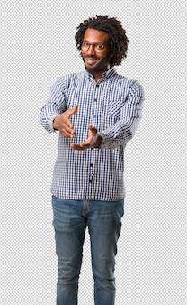Apuesto hombre afroamericano de negocios llegando a saludar a alguien o haciendo un gesto para ayudar, feliz y emocionado