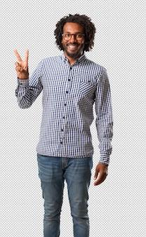 Apuesto hombre de negocios afroamericano divertido y feliz, positivo y natural, hace un gesto de victoria, concepto de paz