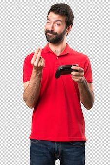 Apuesto joven jugando videojuegos haciendo dinero gesto