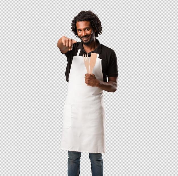 Apuesto panadero afroamericano alegre y sonriente apuntando hacia el frente