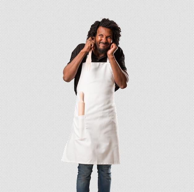 Apuesto panadero afroamericano cubriendo las orejas con las manos, enojado y cansado de escuchar algún sonido