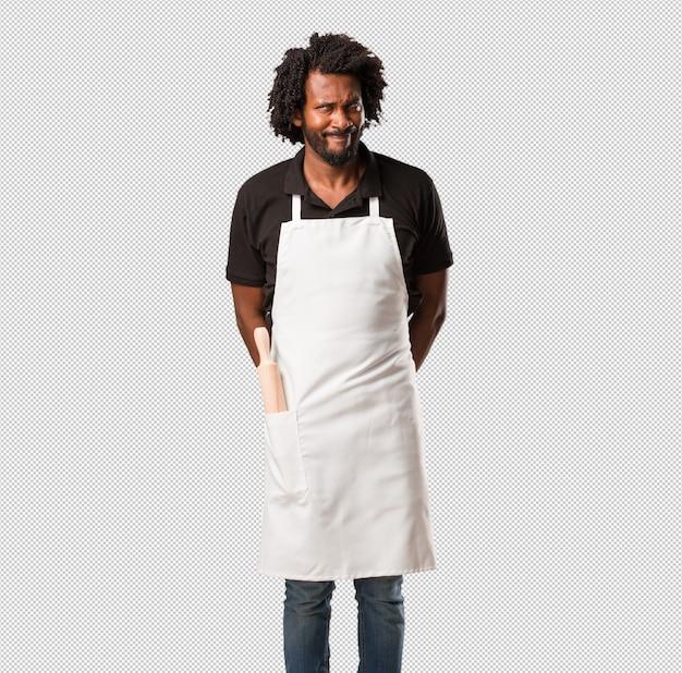 Apuesto panadero afroamericano dudando y confundido, pensando en una idea o preocupado por algo