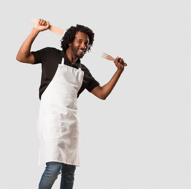 Apuesto panadero afroamericano escuchando música, bailando y divirtiéndose, moviéndose, gritando y expresando felicidad, concepto de libertad
