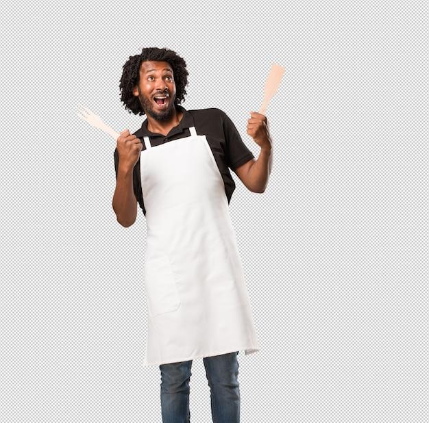 Apuesto panadero afroamericano gritando feliz, sorprendido por una oferta o una promoción, boquiabierto, saltando y orgulloso