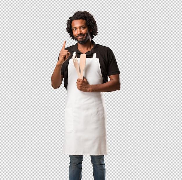 Apuesto panadero afroamericano que muestra el número uno, símbolo de contar, concepto de matemáticas, seguro y alegre