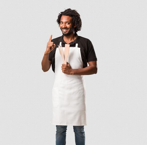 Apuesto panadero afroamericano que muestra el número uno, símbolo de contar, de matemáticas, seguro y alegre