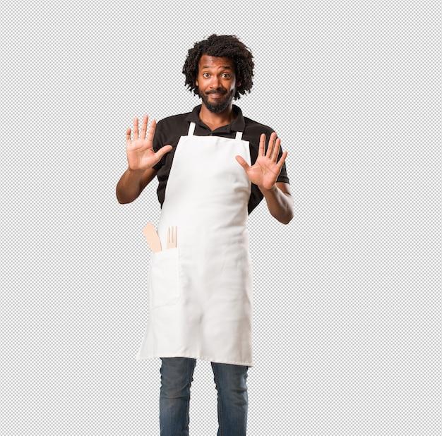 Apuesto panadero afroamericano serio y decidido, poniendo la mano al frente, detener el gesto, negar el concepto